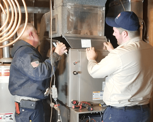 Techs working on a furnace repair